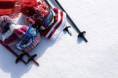 Winter snow sports background with ski poles, goggles, hats and gloves with copyspace .