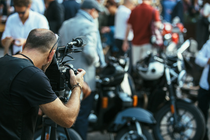 Professional man with camera at motorbike exhibition