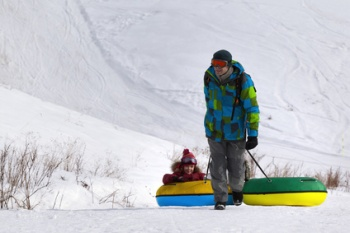 Father and daughter with snow tube at ski resort