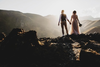 Stylish young wedding couple has fun posing in beautiful Georgian mountains