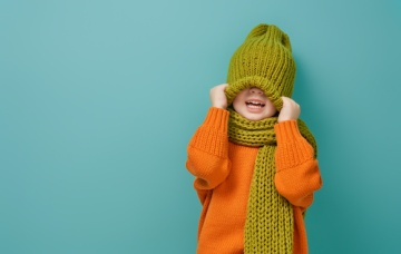 Child with orange sweater and green hat and scarf